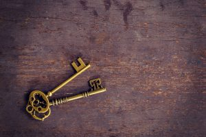 Old gold key vintage on wood background with space.
