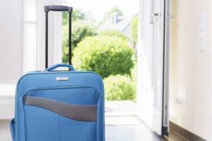 Blue suitcase in front of unlocked open door