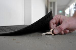 A key placed under a welcome mat